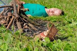 The man was poisoned by mushrooms collected in the forest.  Lies unconscious near the fire, nearby are scattered poisonous mushrooms from a basket. Concept: food poisoning of the body with mushrooms.