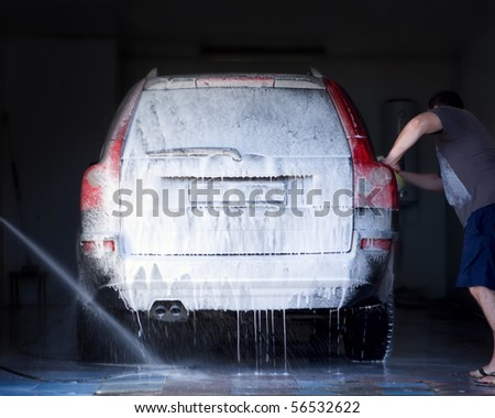 The man washes the car