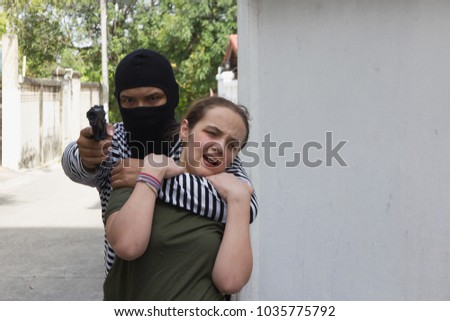 The man wear stripes and wear veils carrying gun.The thief is locking the girl's neck as a hostage.Women wearing green t-shirts are scared. #1035775792