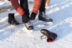 The man wears a winter skates at the rink. Humans disguises shoes on skates.