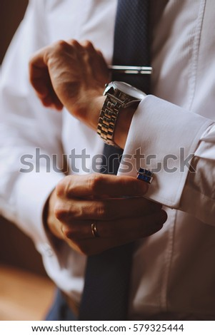 The man wears cufflinks on a white shirt. Men's watch #579325444