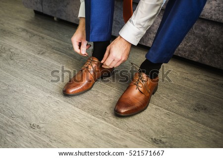 The man wears shoes. Tie the laces on the shoes. Men's style. Professions. To prepare for work, to the meeting. #521571667