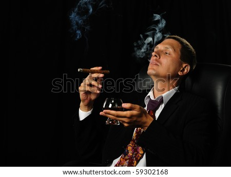 The man with a cigar and a glass of cognac. A dark background - stock photo