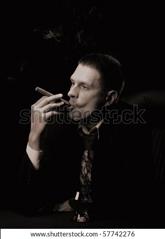 The man with a cigar and a glass of cognac. Monochrome tone. A dark background