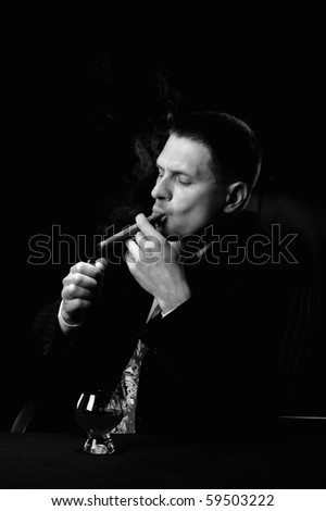 The man with a cigar and a glass of cognac. Monochrome tone. A dark background - stock photo