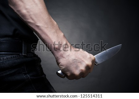 The man with a knife in a hand. Closeup