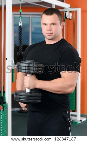 The man with dumbbells in sports club - stock photo