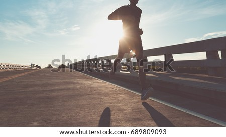 The man with runner on the street be running for exercise. #689809093