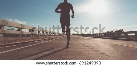The man with runner on the street be running for exercise. #691249393