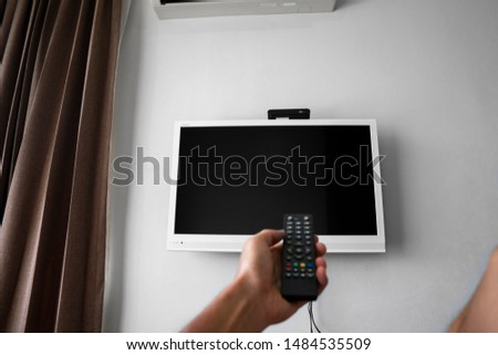 The man with the remote control in hand want switch on the TV and presses the button on the remote control. Remote control in hand closeup. #1484535509