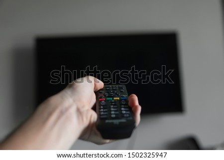 The man with the remote control in hand want switch on the TV and presses the button on the remote control. Remote control in hand closeup. #1502325947