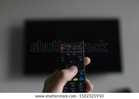 The man with the remote control in hand want switch on the TV and presses the button on the remote control. Remote control in hand closeup. #1502325950