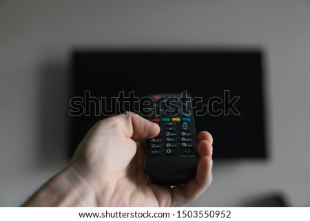 The man with the remote control in hand want switch on the TV and presses the button on the remote control. Remote control in hand closeup. #1503550952