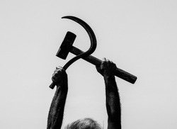 The man working in the field posed with a sickle hammer, the symbol of Communism.