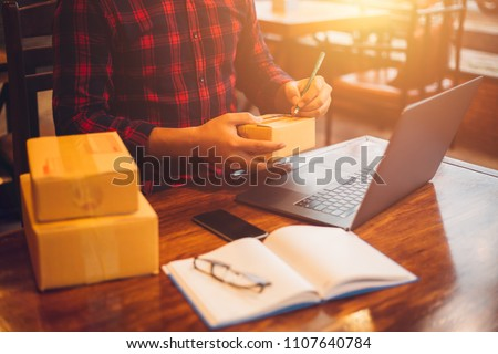 The man working laptop computer from home on wooden floor with postal parcel, Selling online ideas concept.