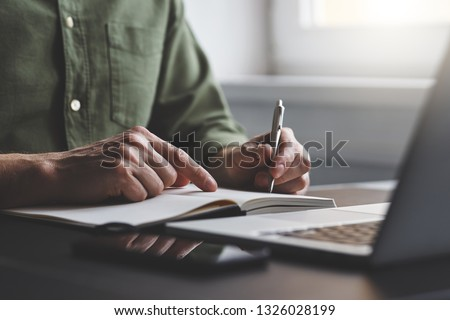 The man writes notes to his diary in the office