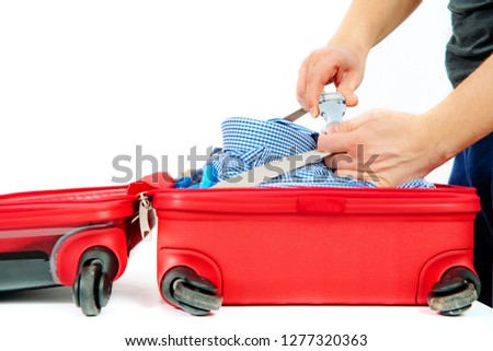 The man zips the security in the suitcase. Travel concept, packing up before departure. Preparing for travel, going on vacation, break, rest. Business trip, delegation. #1277320363