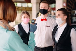 The Manager of a restaurant or hotel checks the body temperature of the staff with a thermal imaging device