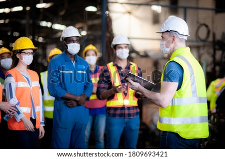 The manager or leader team is assignmenting a job for team of technicians, supervisor, foreman and engineers In the morning meeting before work In which everyone wear masks to prevent the coronavirus ストックフォト ©