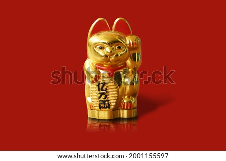 The maneki-neko (招き猫, lit.'beckoning cat') with text mean rich 1 billion Japanese figurine which is often believed to bring good luck to the owner. In modern times,  ストックフォト ©