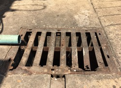 The manhole cover on the sidewalk is rusty and decayed. Dangerous for pedestrian users