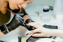 The manicure master in the beauty salon performs the procedure of coloring the client's nails. Women's fashion and beauty. Self-care.