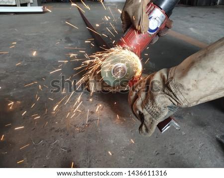 The manual worker cutting metal.