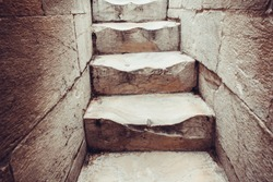 The marble steps are worn from people walking up the spiral staircase inside the leading tower of Pisa, Italy.