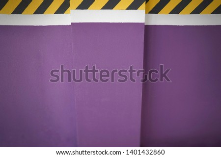 the markings drawing attention to the wall are painted in yellow and black stripes, with a purple background divided by a white stripe #1401432860