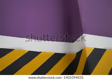 the markings drawing attention to the wall are painted in yellow and black stripes, with a purple background divided by a white stripe #1403394035
