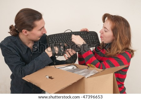 The married couple has opened a cardboard box where the computer is packed.
