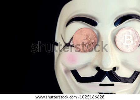 Stock Photo THE Mask symbol for the online hacktivist group Anonymous with Copper bitcoin coins on black background.