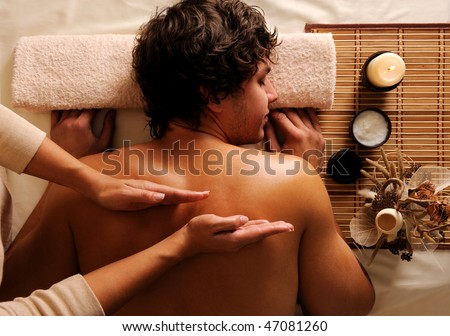 The masseur does back massage to the young guy in a beauty salon