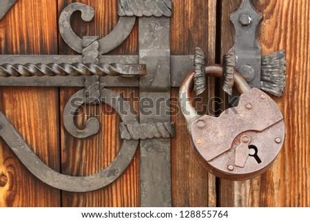 The massive iron lock on wooden gate/Old padlock on a wooden door