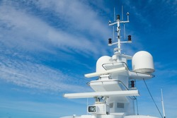 The mast of a large yacht with navigation equipment bottom view. Radar, signal lights, satellite dishes and equipment.