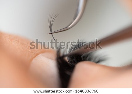 The master builds up large colored eyelashes to the client. Preparation for beauty photography. Creating an image.