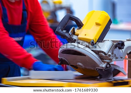 The master cuts a stone slab with a circular saw. Circular saw for cutting stone and tiles. A man next to a circular saw. A person works with tiles. Equipment for stone processing. Mason at work.