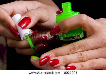 The master does manicure to the girl of bright green color - stock photo
