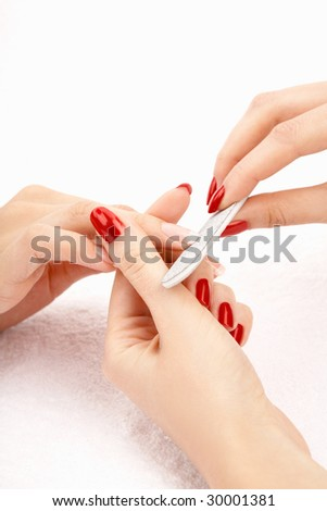 The master files nails on hands to the client, isolated - stock photo