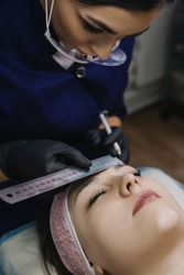 The master in a protective mask in black gloves holds a metal ruler over the eyebrows of a girl who has her eyes closed and looks at the model's eyebrows.