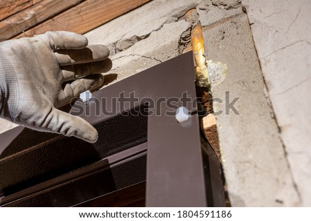 the master installs the front door with a metal box to them, inserts white plugs into the door frame, close-up. fasteners jamb Photo stock ©
