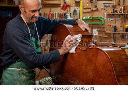 The master luthier builds a double bass in his workshop #501455701