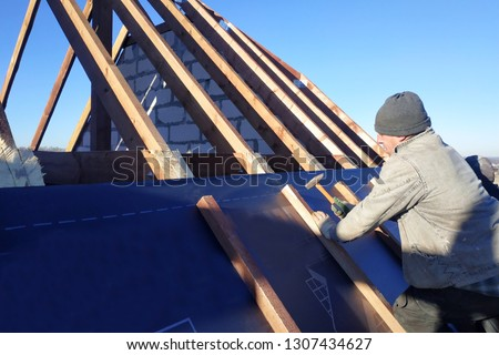 The master nails the bars, fixing this gidrorizer to the rafter, the blue sky appears on the background #1307434627