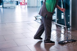 The master of cleanliness conducts a wet mop in the common area. Wet cleaning of tactile tiles in a public area
