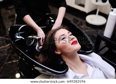 The master of hairdresses washes the girl hair before a hairstyle #649283596