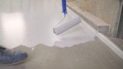 The master paints the floor with white paint. Application of white paint to the concrete floor. Primer for concrete floor before finishing. Repair in the house. Copy space.
