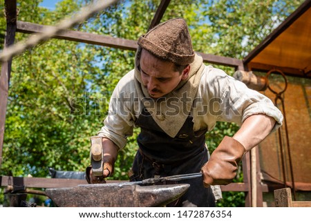 the master works in an old blacksmith's workshop in the open air. reconstruction of ancient crafts and technology of the Middle Ages