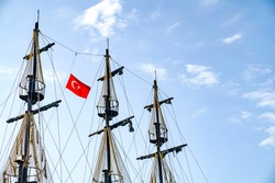 The masts of the ship with the Turkish flag on the background of the blue sky. The concept of travel and freedom