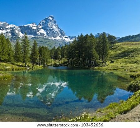 the Matterhorn reflected in the clear waters of blue lake, Valtournenche - Aosta Valley