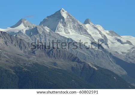 The Matterhorn (right) Dent Blanche (centre) and the Grand Cornier (left) in the southern swiss alps above the val d'herens lit by the setting sun